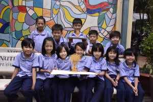 Some Sunshine school children with an Origamo card in Vietnam as part of the company's commitment to the CNFC charity.