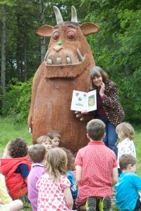 Author Julia Donaldson enthralling children with one of the Gruffalo sculptures that were installed in UK forests.