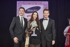 Rachel Hare on stage at The Henries last Thursday collecting the Best Christmas Box or Pack award for Paloma from (right) Nick Henry of sponsor Gould Paper and comedian John Robins who hosted the event.