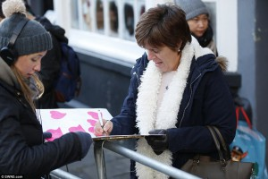 A well-wisher adds her message to the card just before it was presented to Harry and Meghan.
