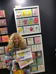 Emily Coxhead with some of the card collection and the feelgood newspaper on Pigment Cards' stand at Spring Fair.