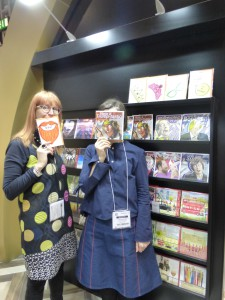 Paper Rose's Reggie Pugh with one of the Say Selfie designs (winner from the 2015 On The Cards) with colleague Phillippa Phipps masked by a Political Pals design on the company's stand at Spring Fair.