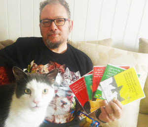 John Higgins with his rescue cat, Freddie and some of the cards they have donated to Cats in Distress.