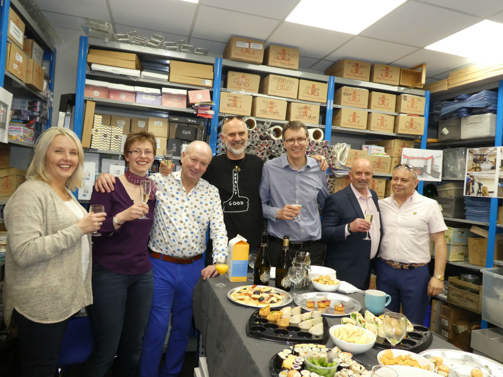 The 'behind the scenes' celebration. The super tidy stockroom was a great party venue. (Left-right) Julie Brightly (The Imaging Centre), Lisa Shoesmith (Really Good), Warren Lomax (PG), David Hicks (Really Good), Nigel Williamson (House of Cards), Derek Hanley (Unique) and Miles Robinson (House of Cards).