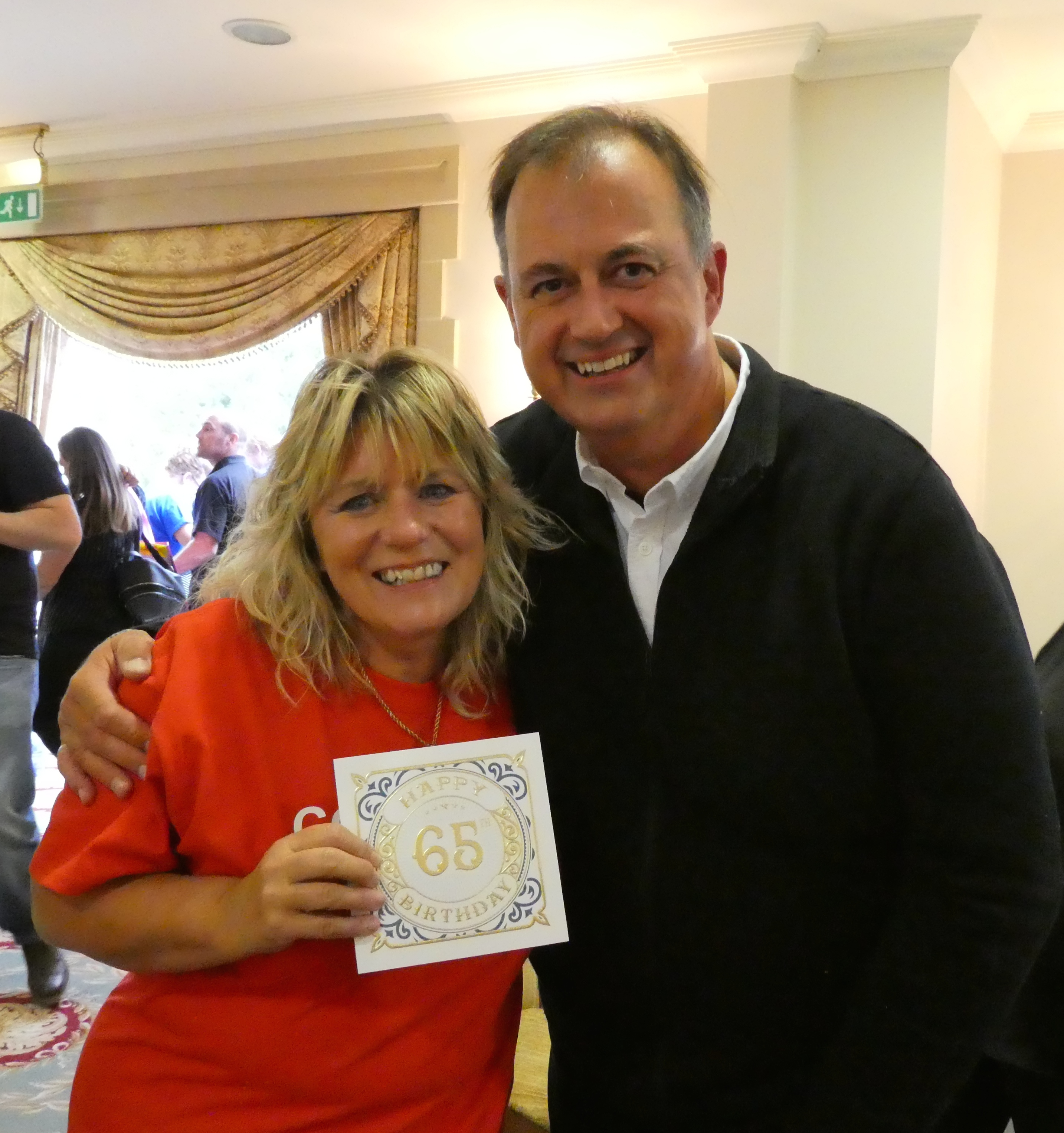 Paul Woodmansterne with Caroline Lawson, valued member of the publisher's sales team receiving one of the special company 65thcards.