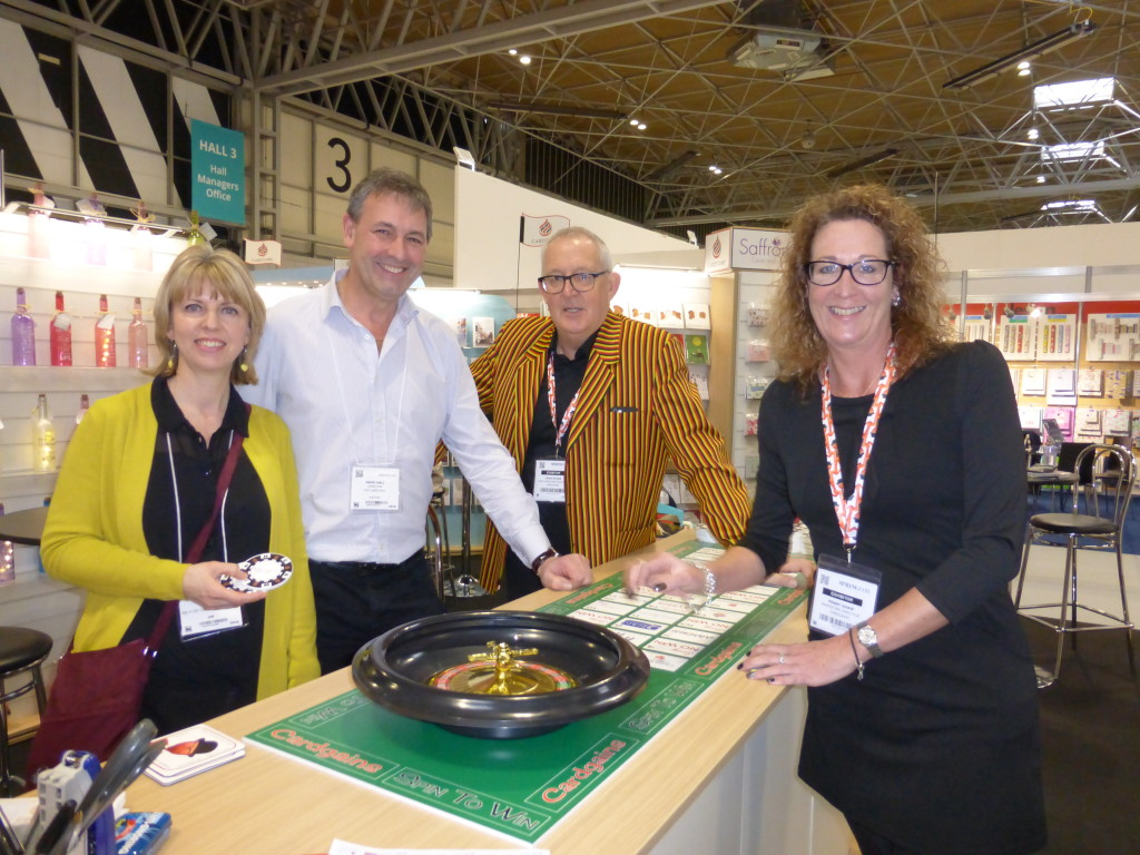 Above: There will be a different Wheel of Fortune type activity on the Cardgains Village at Spring Fair this year reveals Penny Shaw (pictured right) with co-director Chris Dyson (second right) and members David and Kate Hall of The Card Hall with the 'win win' roulette wheel at the show last year.