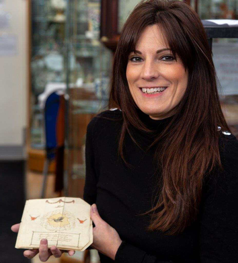 Above: Hansons' Helen Smith holds the delicate Valentine that dates back to 1790-1810 that is now owned by PG's Jakki Brown.
