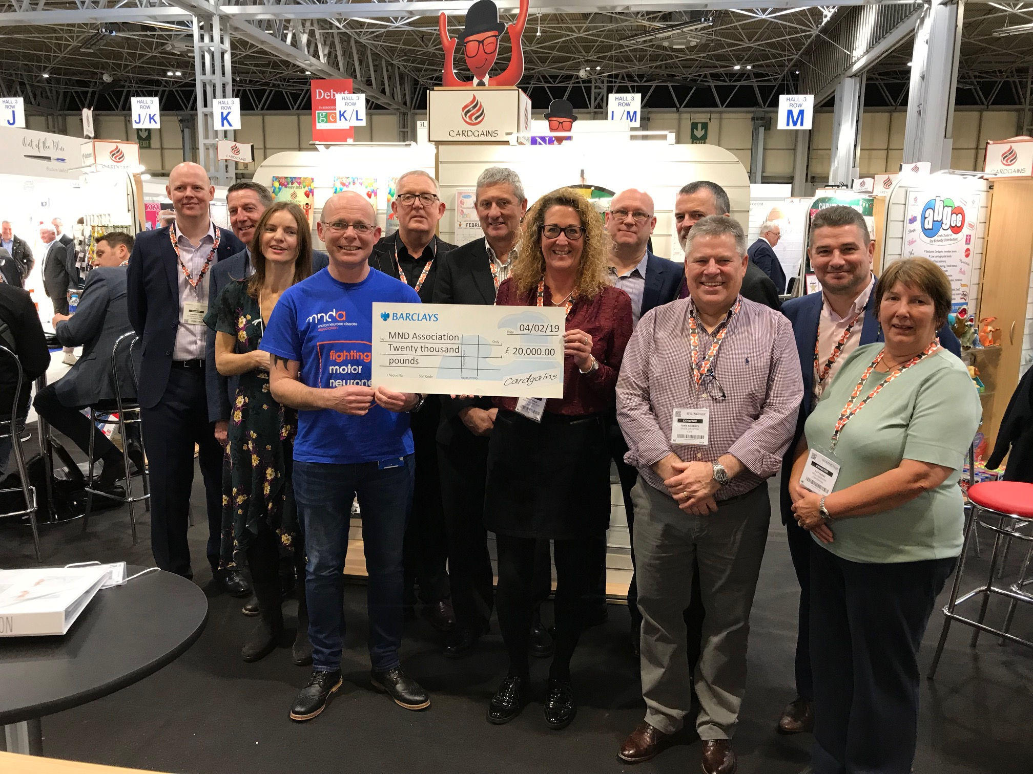 Above: The Motor Neurone Disease Association was delighted to be presented with a giant cheque for £20,000 from Cardgains as a result of the fundraising by the buying group in 2018, largely through its annual charity challenge, a mega walk in Cumbria undertaken by many publisher suppliers and retail members, many of whom were there for the chaque handover.