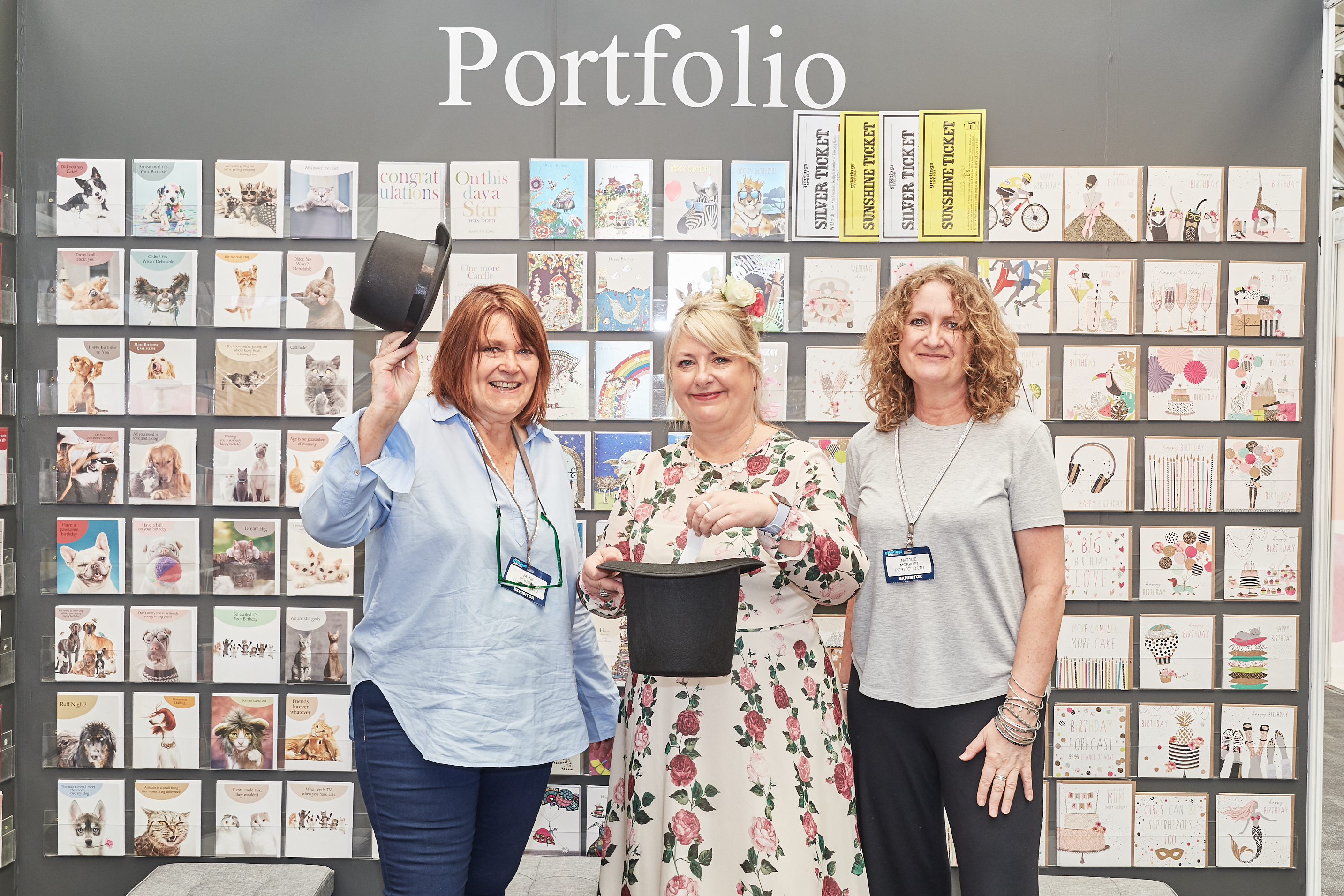 Above: The names of all retailers who have registered on Portfolio's new trade website were put into a rather impressive hat. Portfolio's Jayne Diggory (left) and Natalie Morphet (right) invited PG's Jakki Brown to delve deep and pick out the winning names. The first prize of a carriage free order was won by Wickwire of Sheffield while 36 free Father's Day cards are winging their way to the two runners-up – The Scandinavian Shop in Helensburgh and Unique Creations in Oxford.