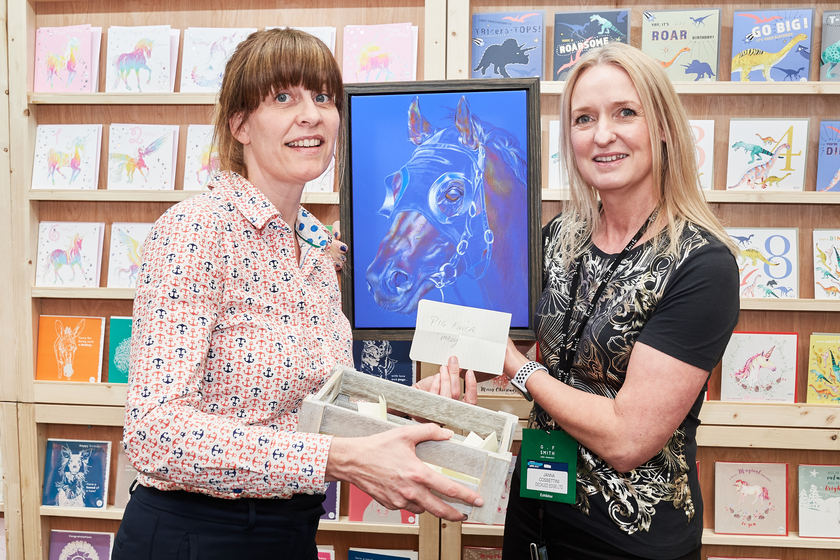 Above: The framed canvas of a beautiful racehorse, created by artist Janna Cossetini, founder of Deckled Edge (right), was won by Pig Finca in Kingsbridge, Devon. PG's Gale Astley (left) made the prize draw.