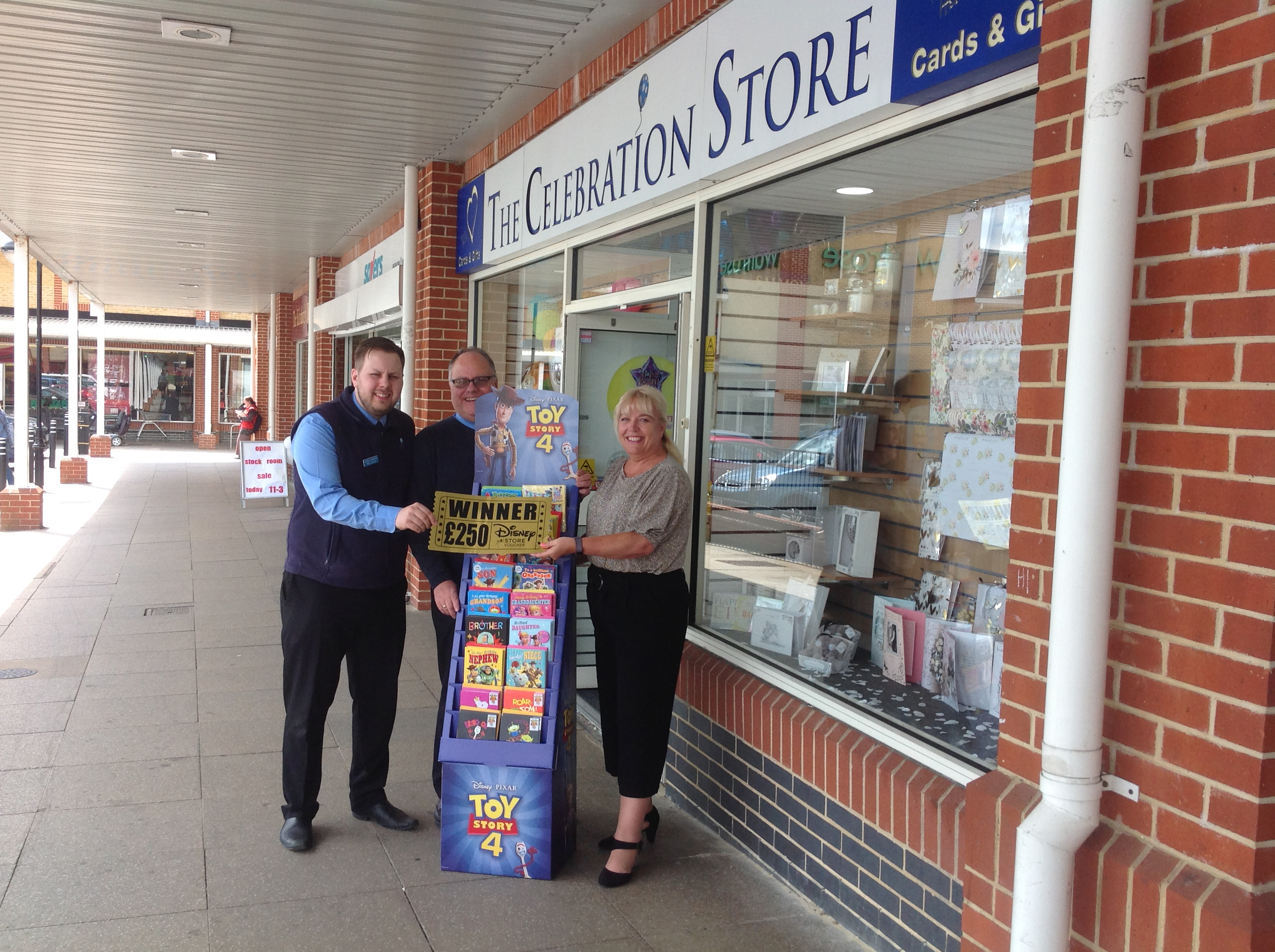 Above: (left-right) Ryan and Chris Jenkins with UKG sales exec Tracey Markham outside the store with the Toy Story display unit and prize voucher.