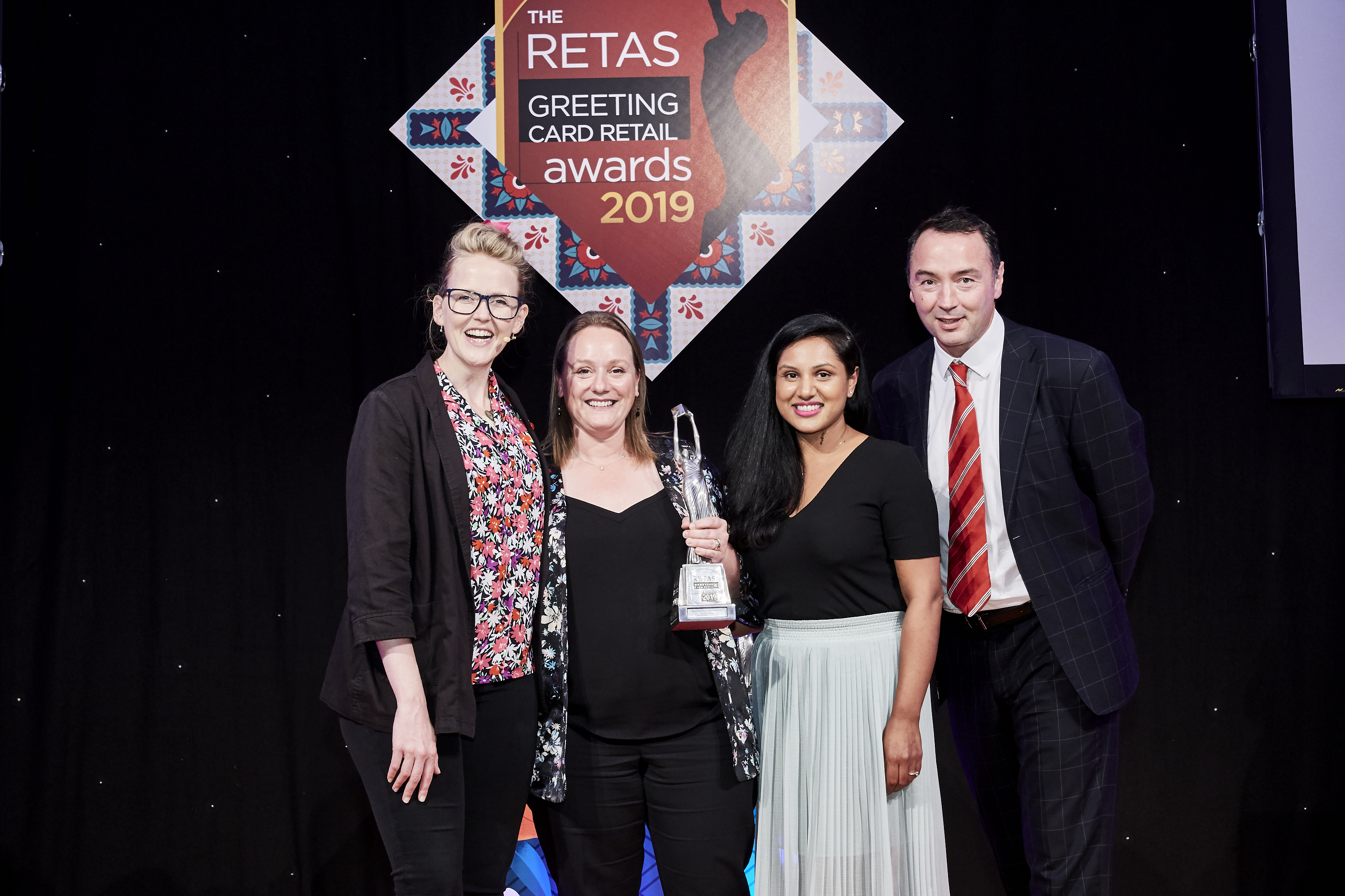 Above: John Lewis & Partners' buyer Lisa Rutherford (second left) and merchandiser Payal Shah were presented with the trophy by Nick Carey, managing director for Abacus Cards, the category sponsor.