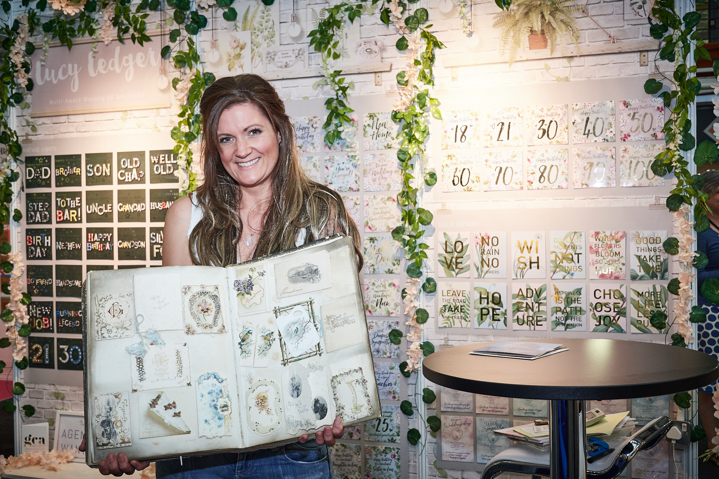 Above: Lucy Ledger on her stand at PG Live this year with her treasured album of historic greeting cards.