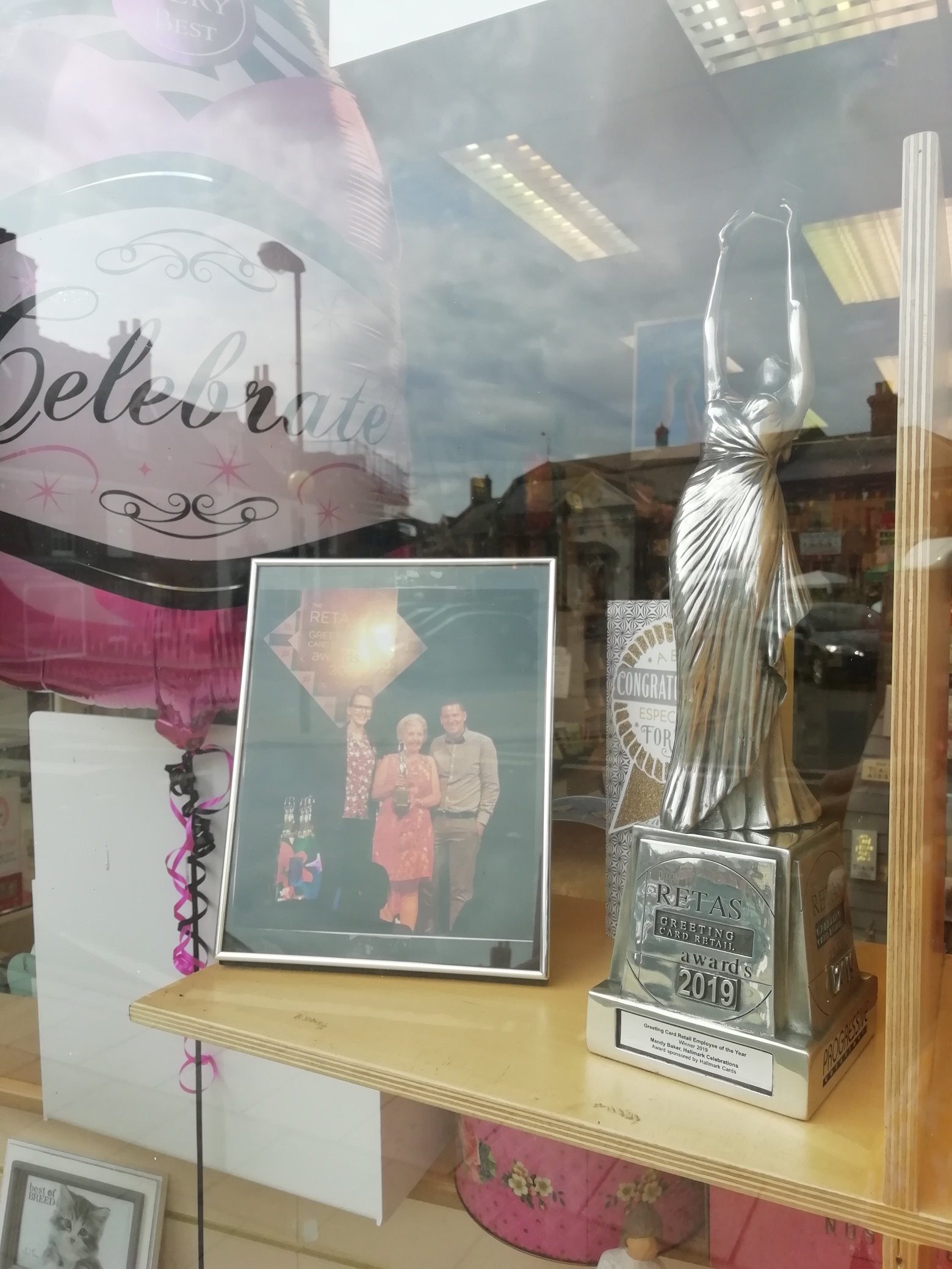Above: The trophy in pride of place in Celebrations' window in Aylsham together with the photo of Mandy Baker, who won the Best Retail Employee award.