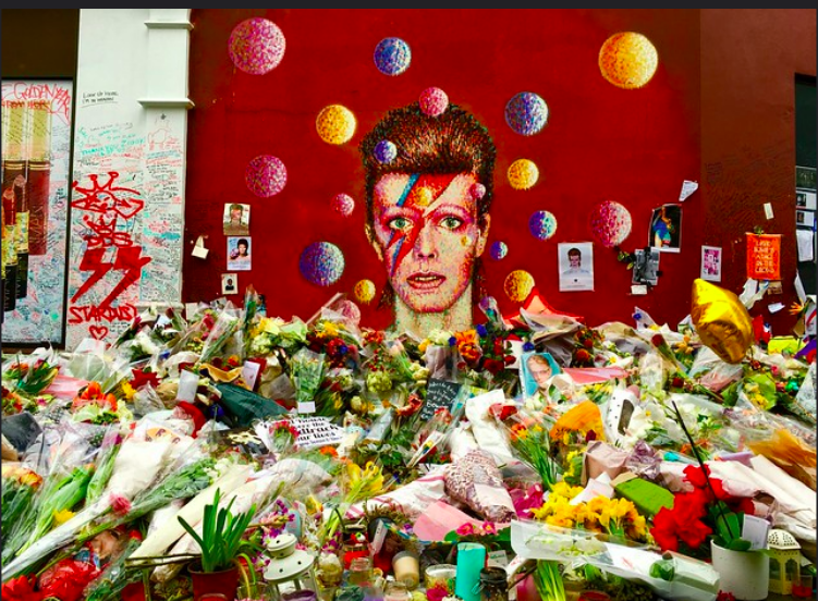 Above: A David Bowie mural that is on the outside wall of Morley's Brixton store where many Bowie fans leave flowers and notes in tribute to him.