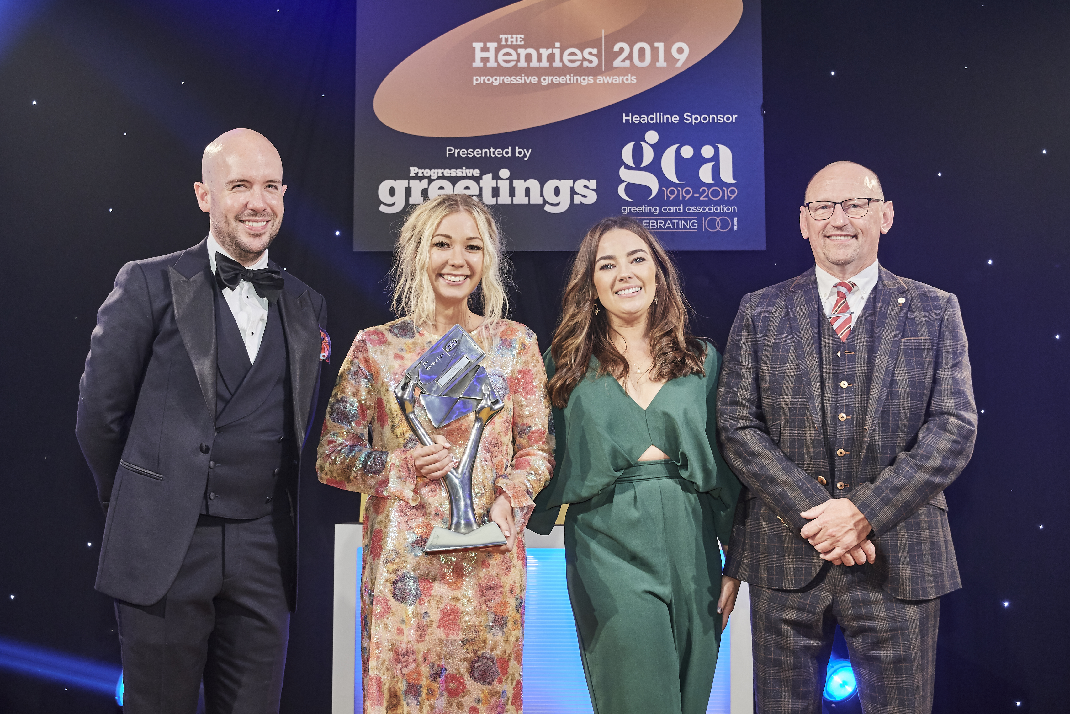 Above: Emily Coxshead, founder of the Happy News was all smiles as she collected the trophy with Sam Wilson, senior designer for Pigment that was presented to them by Skeet Print's director, John Skeet, sponsor of this award category.