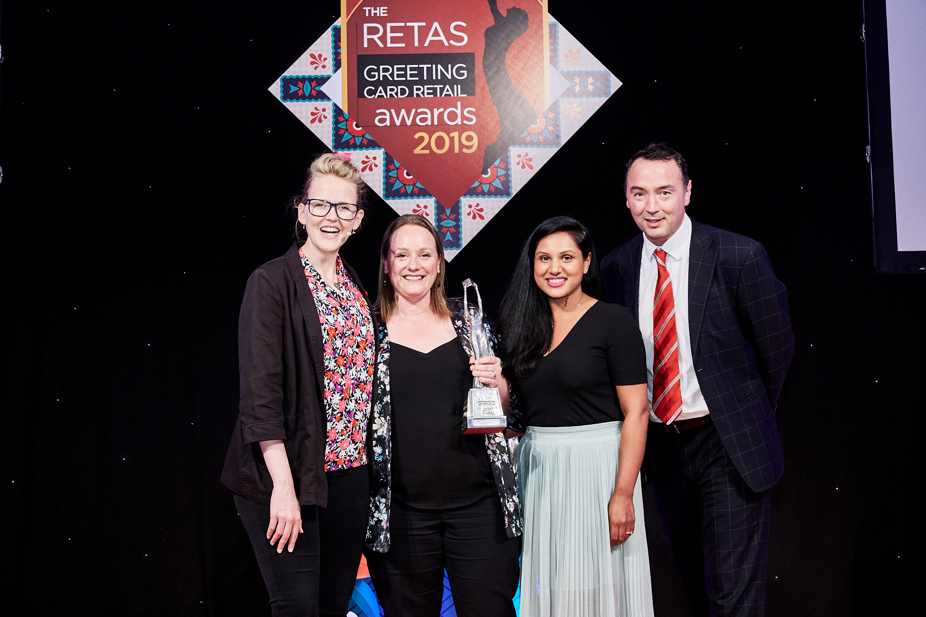 Above: Having been awarded Best Department Store Retailer of Greeting Cards in The Retas 2019, John Lewis' Lisa Rutherford (second left) and merchandiser Payal Shah collected trophy from Nick Carey, managing director for Abacus Cards, the category sponsor. Pippa Evans, who hosted the event is pictured far left.