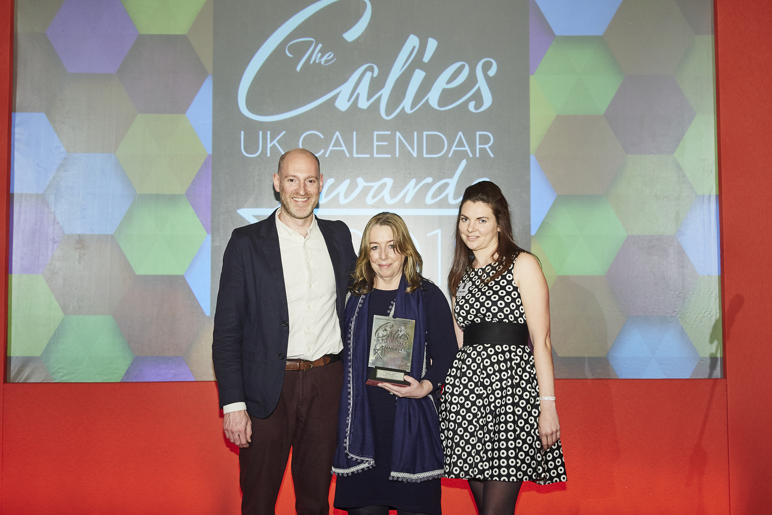 Above: Heather Marten (centre) collecting the Best Generic Diary award at The Calies 2018 for English Graphics Inkwell + Feather design from Calendar Club buying manager Becky Salter and host Henry Paker.