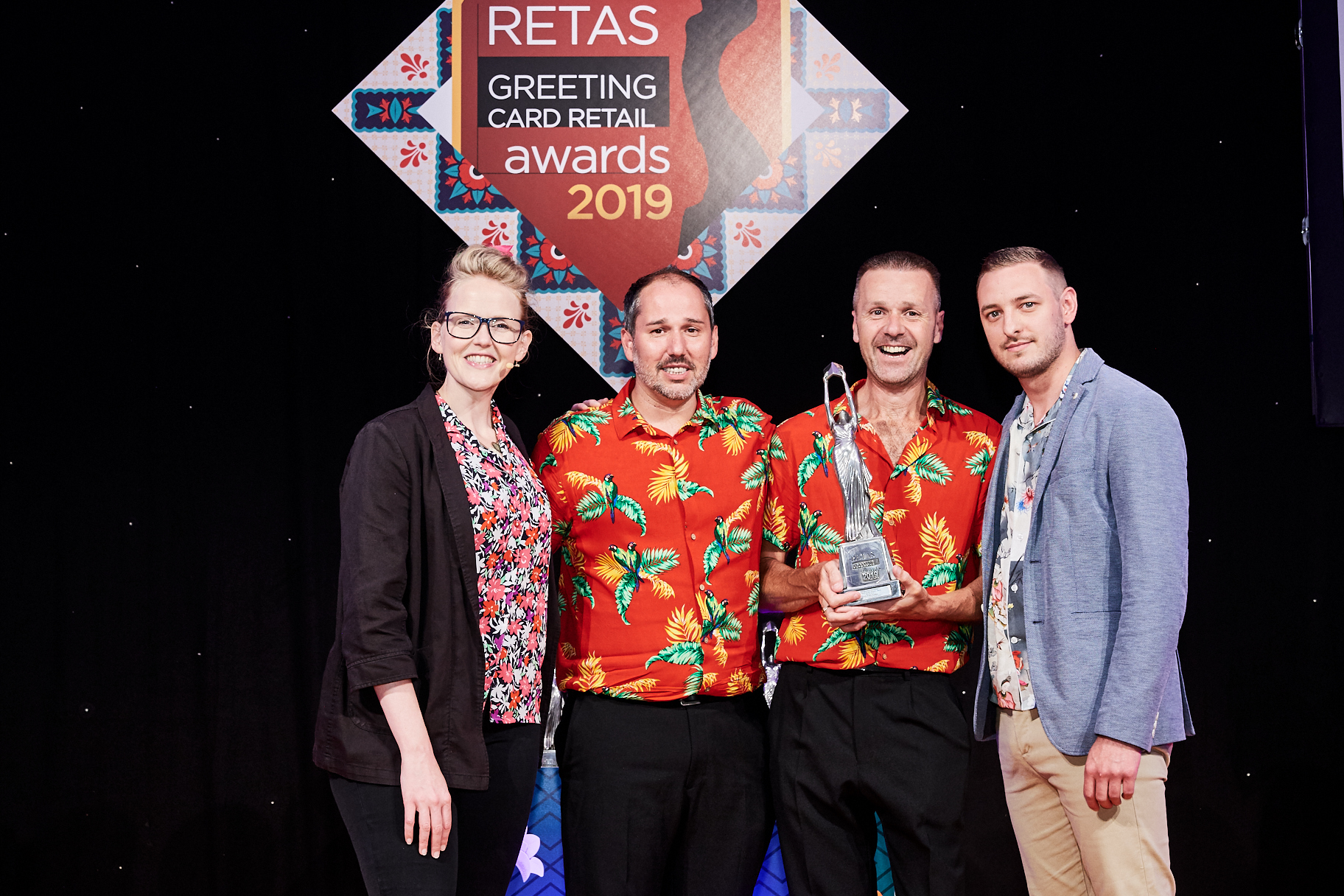 Above: Carl Dunne (2nd right) and his partner Oliver Guise-Smith (2ndleft) collecting the retailer's award at The Retas from Paper Salad's Jack Wilson, sponsor of the category who was on stage with Pippa Evans, host of the event.