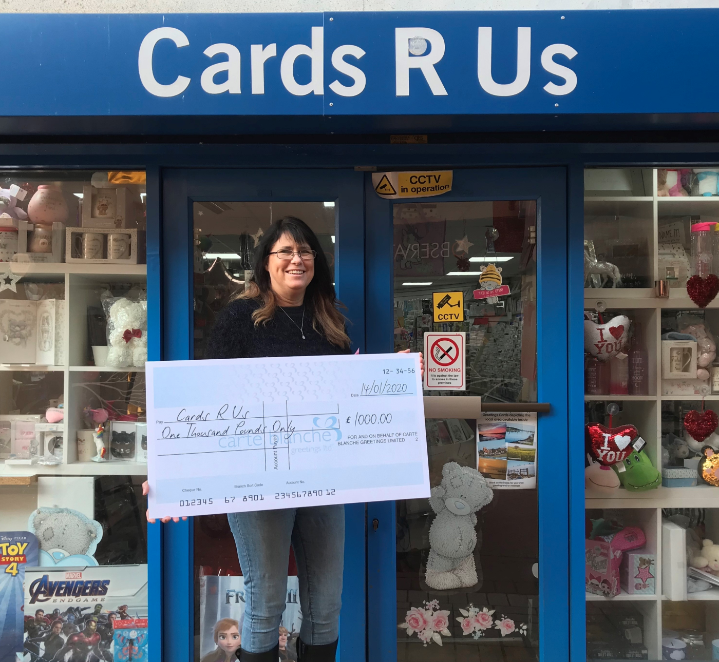 Above: Cards 'R' Us' co-owner Amanda Lockwood outside the South Woodham Ferrers' shop with her big cheque from Carte Blanche.