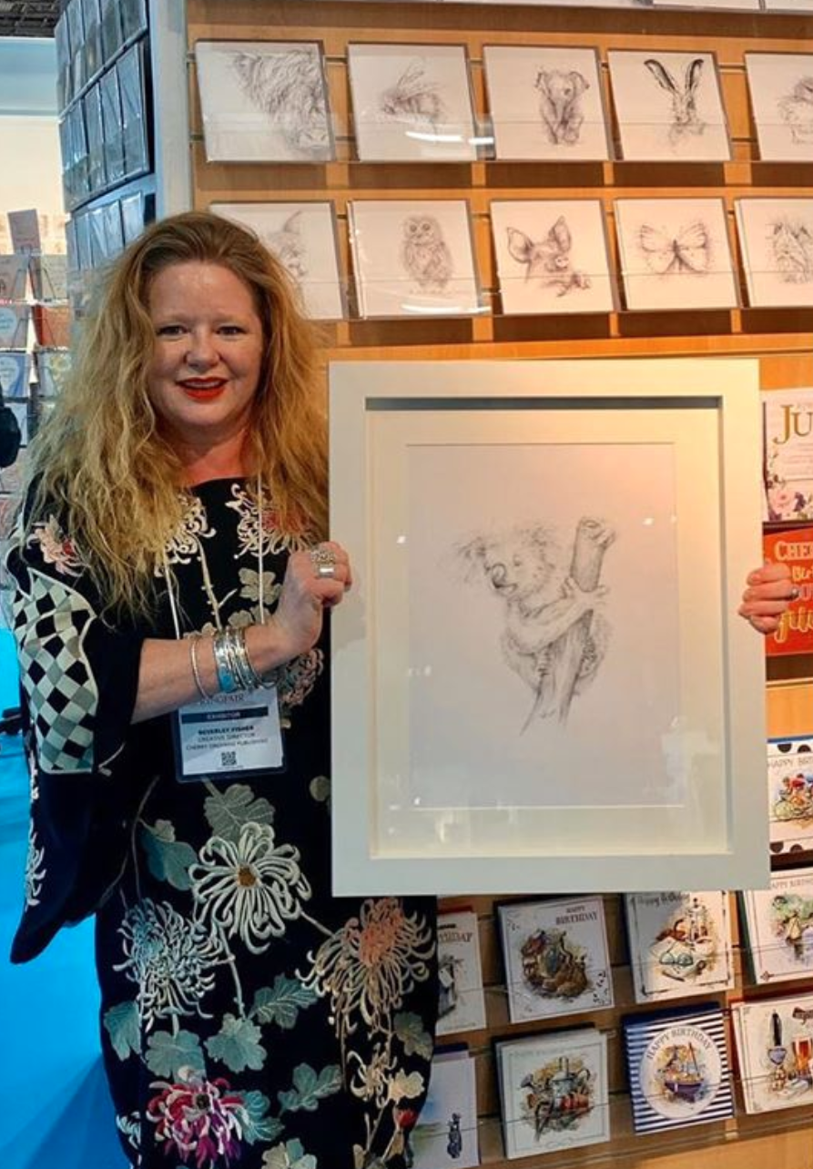 Above: Cherry Orchard's creative director Bev Fisher with the framed original drawing she created which was raffled off at the recent show, raising almost £700.