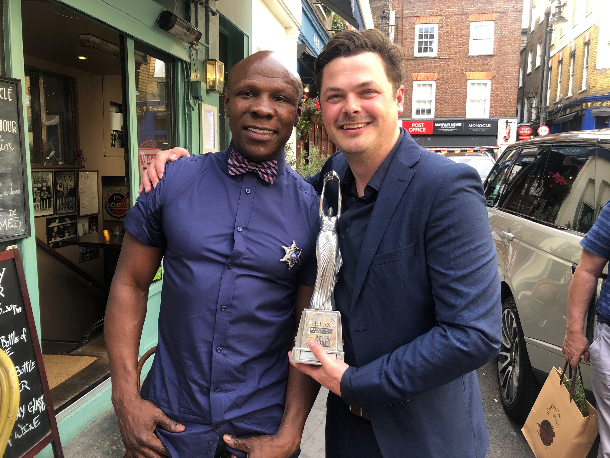 """Above:Budget Greeting Cards' operations manager, Mike Spencer (right) pictured with The Retas 2019 trophy for Best Greeting Card Wholesaler with Chris Eubank – who congratulated Mike on the award on the day of The Retas, telling him he is """"only photographed with winners""""."""