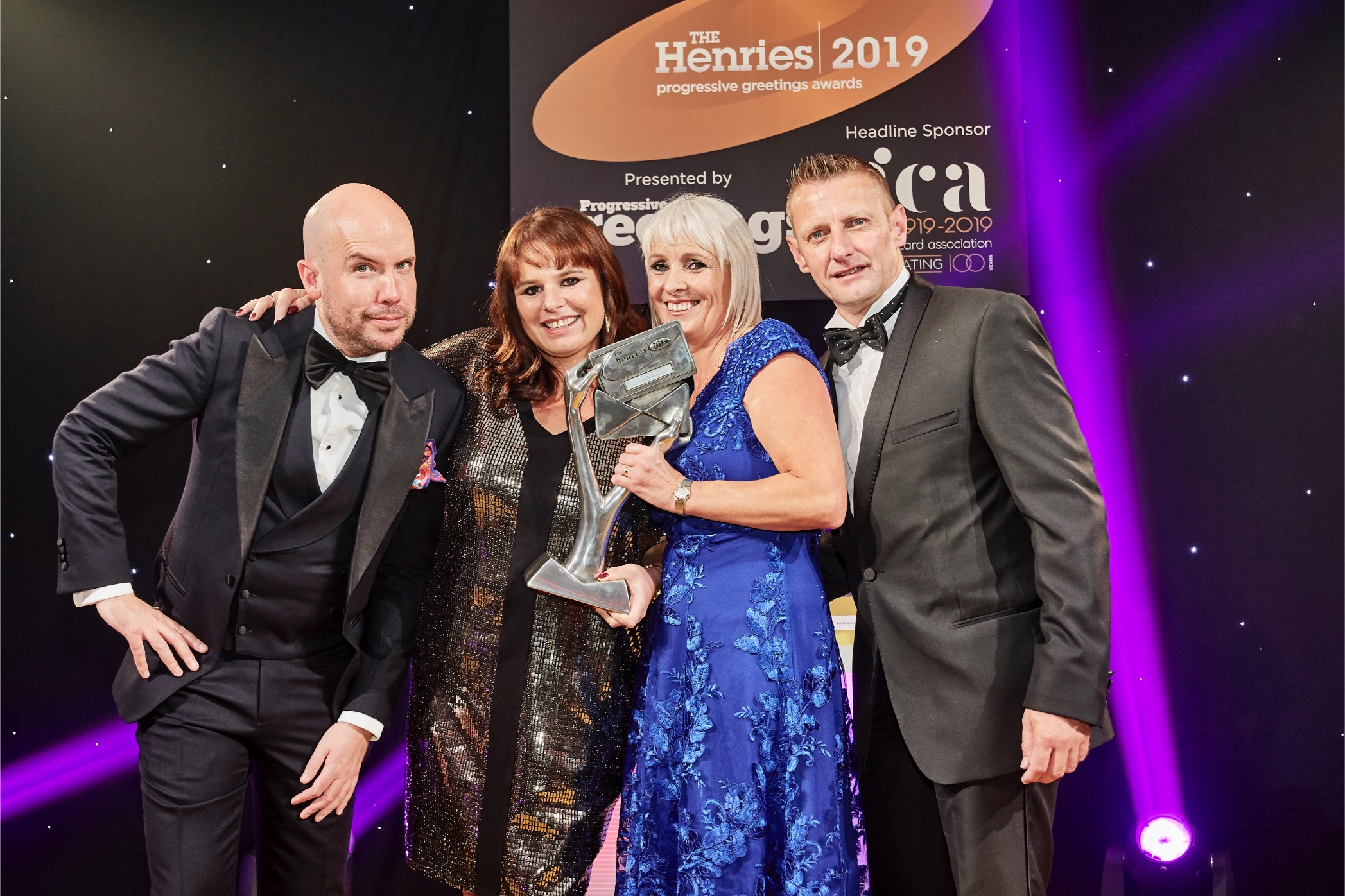 Above: Paper Salad's Claire Williams (second left) and Karen Wilson collecting their Henries award for its Children's Jamboree range last October. On stage with (far left) Tom Allen (host) and Loxley's md Tony Lorriman, sponsor of the award category.