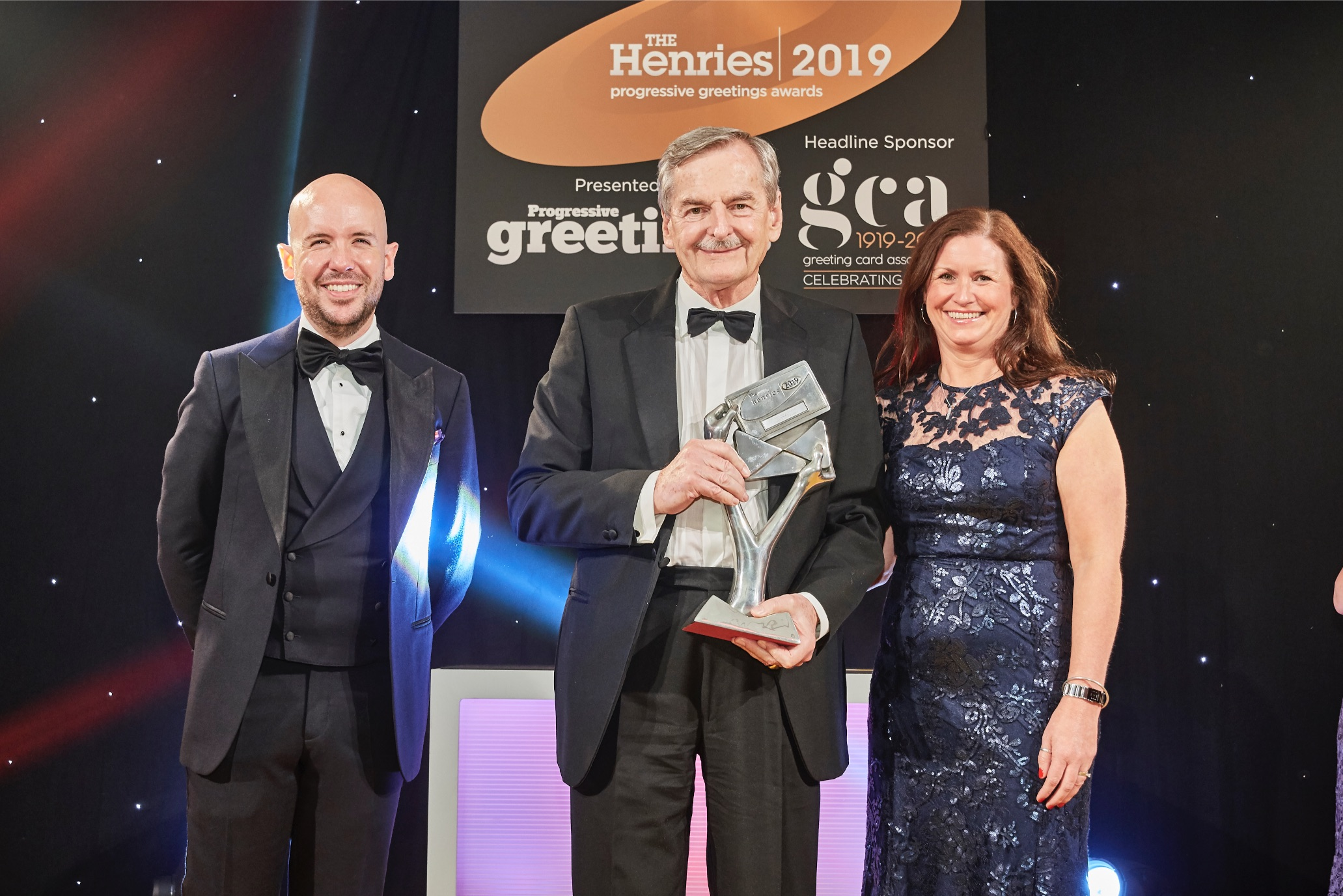 Above: Last year, in recognition of the GCA's 100th anniversary, instead of the Honorary Achievement Award, Simon Elvin (centre) was presented with a special GCA Outstanding Contribution. Pictured with Joanne Davis of UK Envelope Centre, sponsor of the award category and The Henries' host Tom Allen.