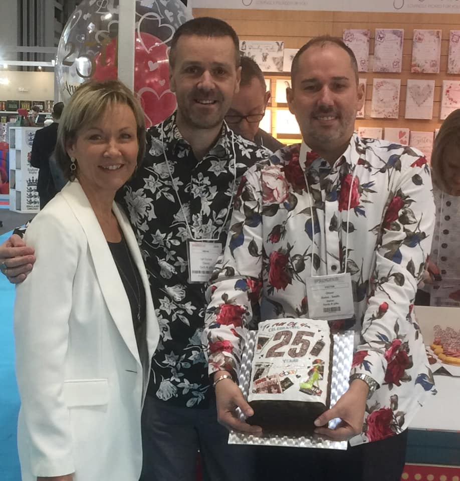 Above: Cherry Orchard's retail customers Carl Dunne and Oliver Guise-Smith of Cards & Gifts Sheffield at the recent Spring Fair at which the chaps presented Jackie Collins with a cake and cupcakes to celebrate the company's 25th anniversary.