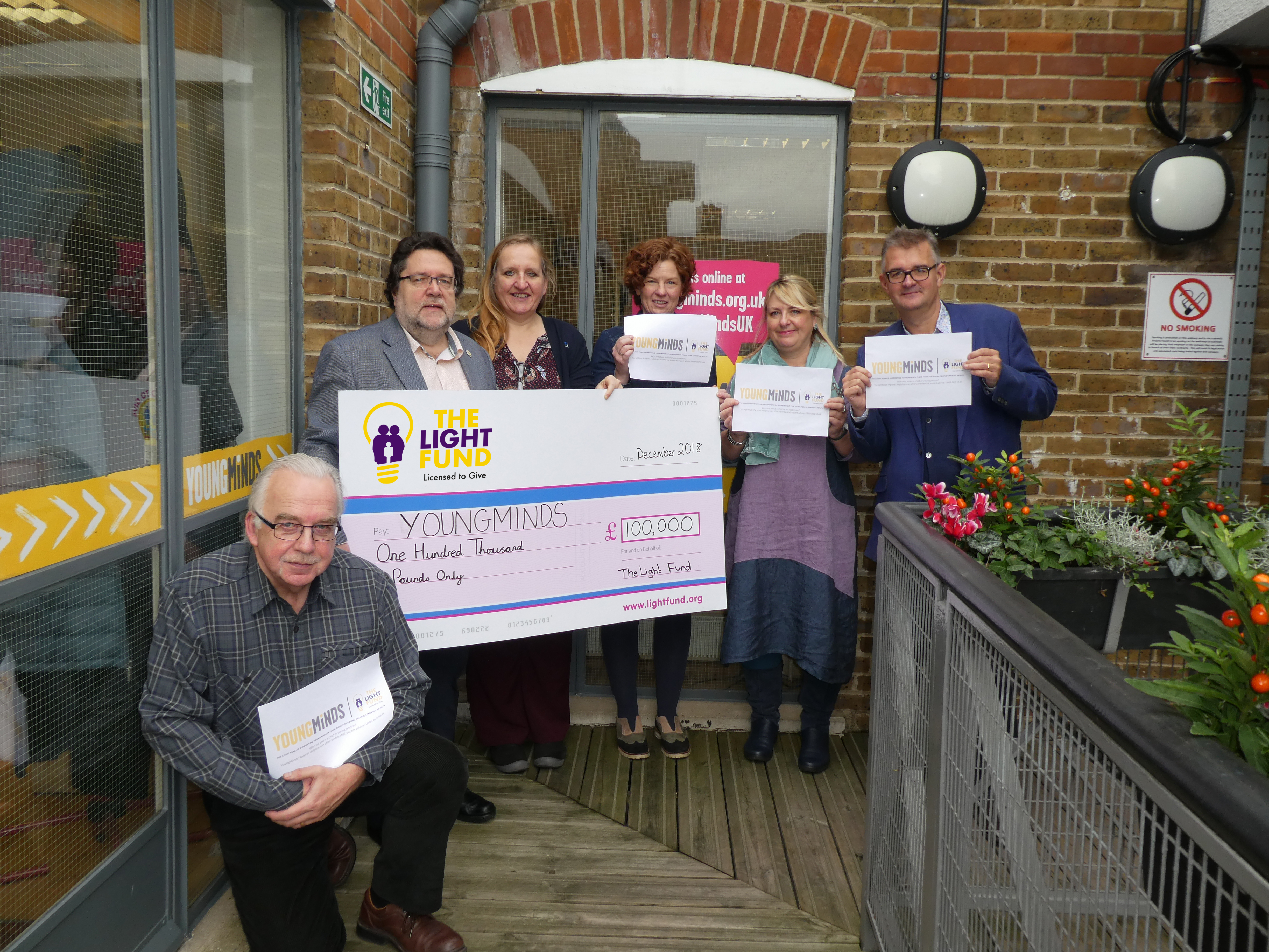 Above: Among the many projects The Light Fund has funded over the years was a two year commitment to Young Minds for its helpline. The Light Fund's chairman Trevor Jones (second left) went with several members of the committee to present the cheque. These included Kelvyn Gardner (front), a long serving Light Fund committee member who sadly died a few weeks ago. (https://www.pgbuzz.net/tributes-flood-in-for-licensing-industry-legend-kelvyn-gardner/)