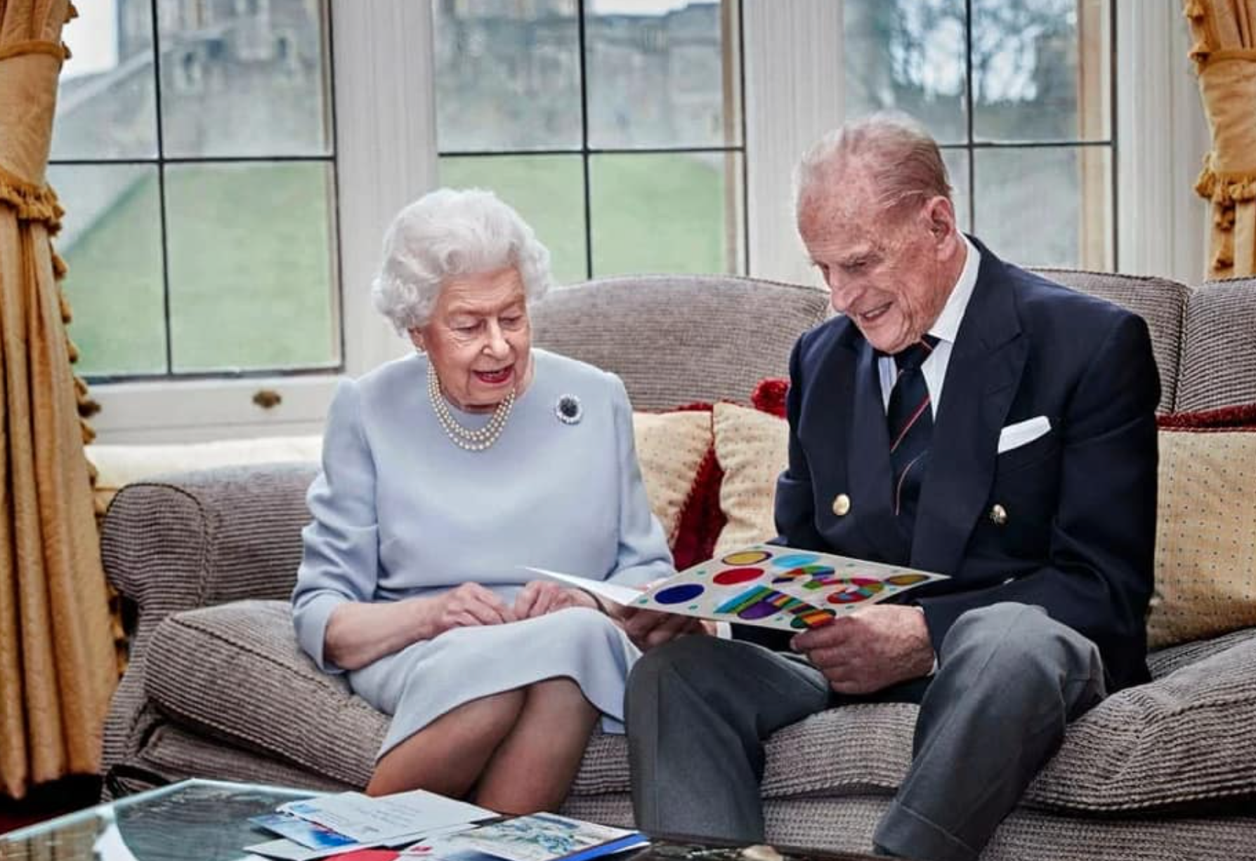 Above: The Queen and Prince Philip showing their delight at the anniversary card that had been made by three of their grandchildren.