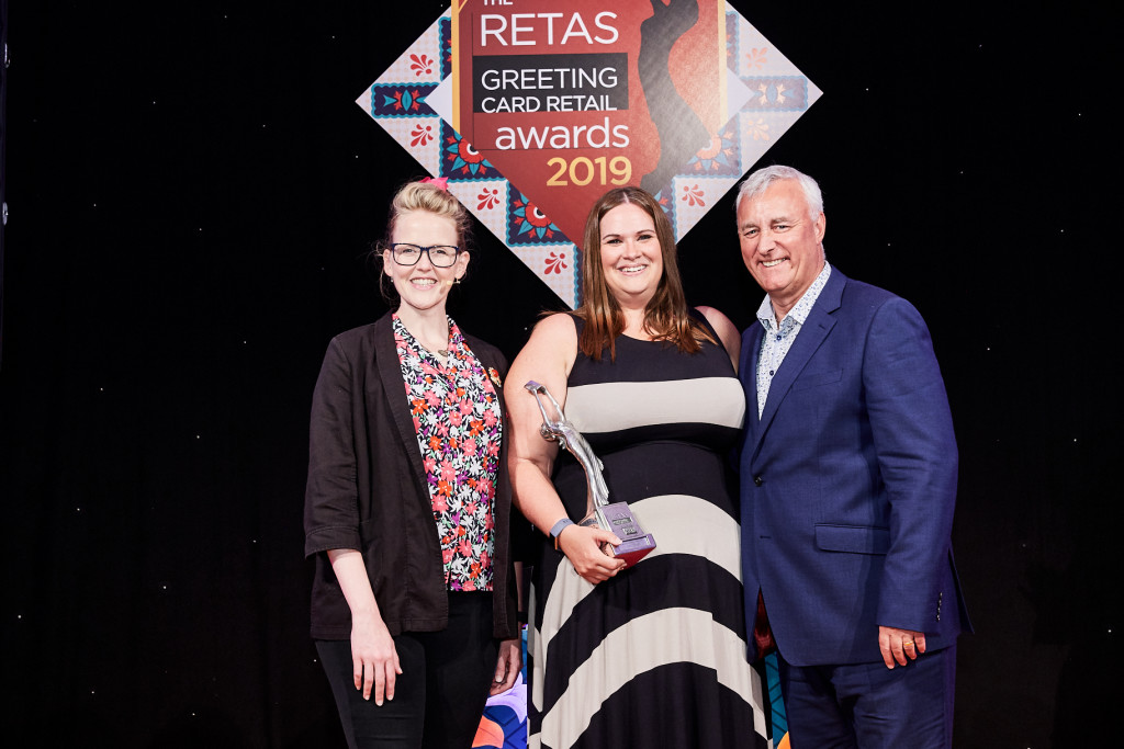 Above: Carly Pearson (middle) collecting the award for Best Supermarket Retailer of Greeting Cards at The Retas 2019 awards from Simon Boyd, operations director of PG Live, sponsor of the award category.