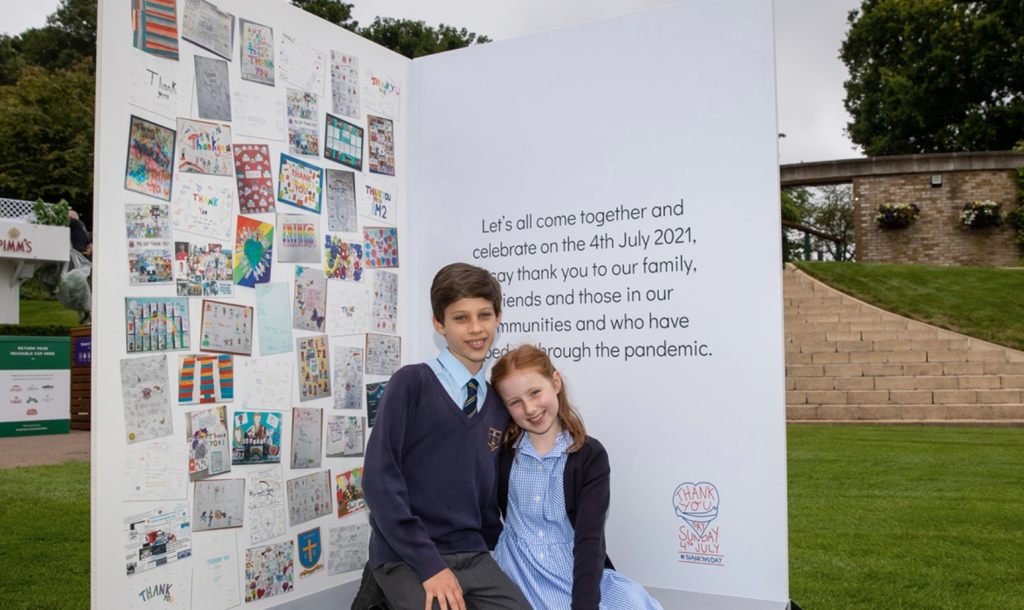 Above: Two school children showing the inside of the card which features designs from different schools.